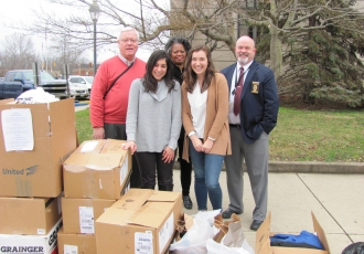 Students Hannah Piscalko (front left) and Elli Schwartz (front right), with epidemiology research associate Deborah Jones (back center), delivering winter clothing to officials in Scioto County.