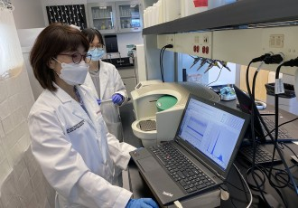 Jiyoung Lee, left, and PhD student Yuehan Ai check SARS-CoV-2 genetic copy data using droplet digital PCR.